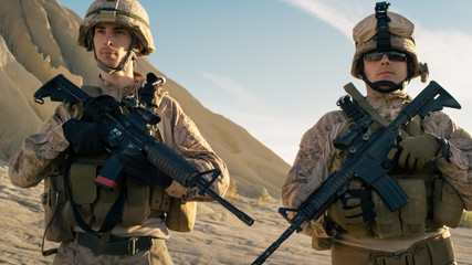 Two Fully Equipped Soldiers Standing in a Line in the Desert.