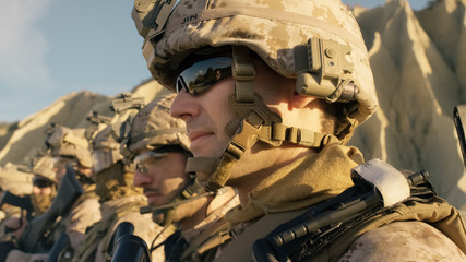 Close-up Shot Group of Fully Equipped Soldiers Standing in a Line in the Desert.