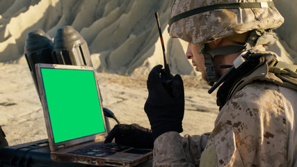 Soldier is Using Laptop Computer with Green Screen and Radio for Communication During Military Operation in the Desert.