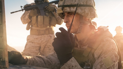 Soldier is Using Radio For Communication During Military Operation in the Desert