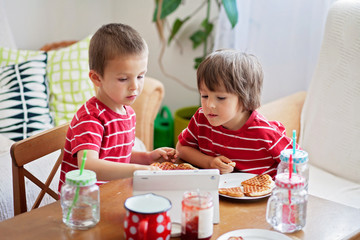 Two small children, boy brothers, eating breakfast at home, while watching cartoon