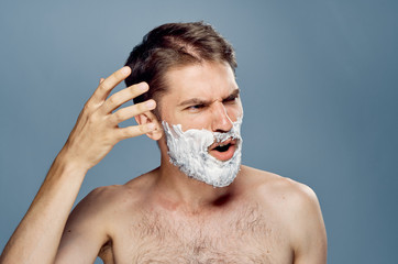 Young guy with a beard on a gray background in shaving foam