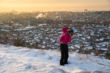 Girl in a red jacket. The tourist takes a picture of the dawn in the morning. A girl in a gray hat takes a picture of the morning city Saratov