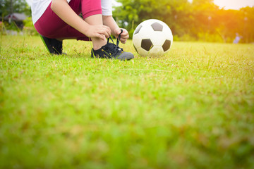 Child Asian tying shoes with ball on green grass.