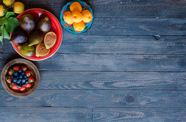 Fresh figs with peaches, apricots, blueberries, strawberries, on a wooden  background.