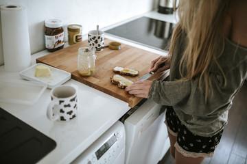 Mädchen schmiert sich ein Brot
