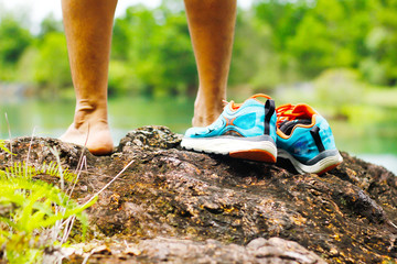 Stock Photo - Shoes on the rocks next to a mountain lake