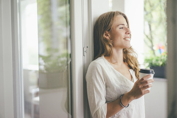 Smiling young woman holding takeaway coffee at the window