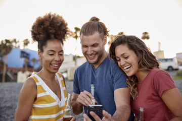 Three laughing friends with beer bottles looking at smartphone on the beach
