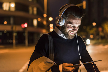 Smiling young man with tablet and headphones on urban street at night Wall mural