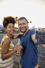 Two friends with beer bottles taking selfie on the beach