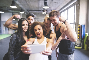 Group of young people posing for a selfie in gym