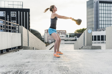 Woman exercising with kettlebell on parking level in the city