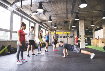 Group of young people watching young man doing push-ups in gym