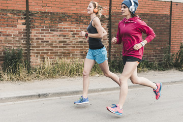 Two women running on the street