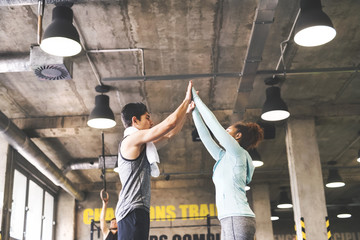 Two young athletes high fiving in gym