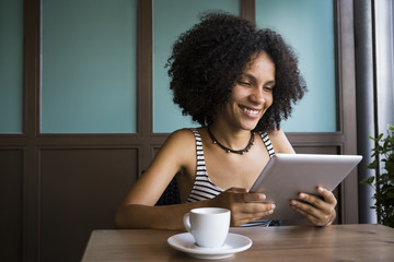 Young woman sitting in a coffee shop looking at tablet
