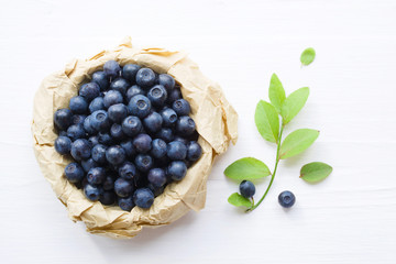 Fresh  blueberries in a cup on a white surface of a table. Closeup, top view.