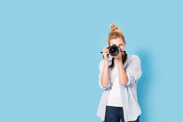 Young blonde photographer is taking a photo. Model isolated on a blue background with copy space