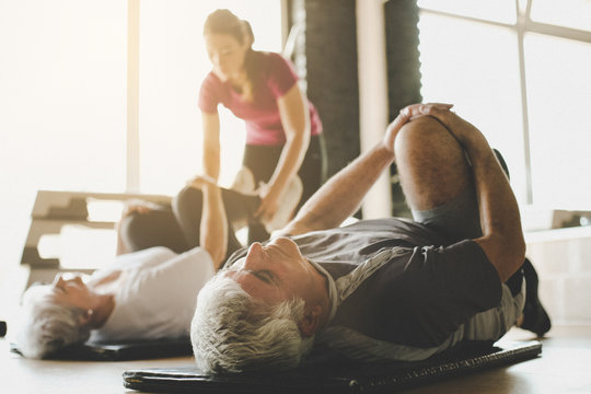Senior couple workout in rehabilitation center. Personal trainer helps elderly couple to do stretching on the floor. Focus on man.