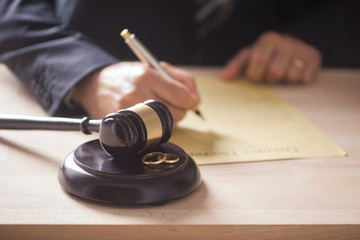 Judge with gavel on table with wedding rings. Divorce concept