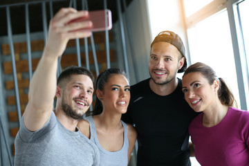 Group of smiling people making self-picture in gym. People workout in gym.