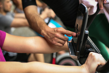 Close up of people hands. Personal trainer changes the speed of the bicycle.