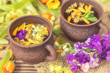 Two ceramic cups of healthy herbal tea with decoction of dry and fresh flowers on dark aged rustic wooden background. Shallow depth of field.