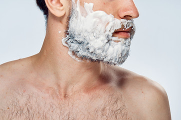 Young guy with a beard on a light background in shaving foam