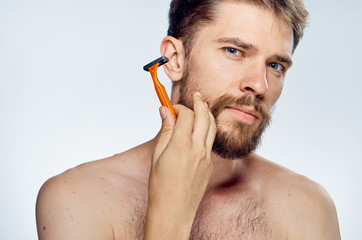 A young guy with a beard on a light background holds a razor
