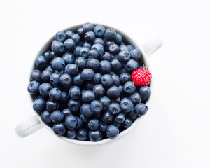 Fresh  blueberries in a cup on a white surface. Closeup, top view.