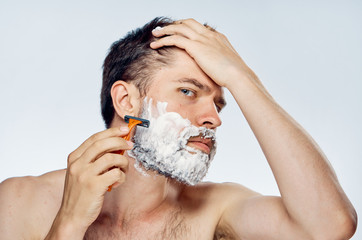 Young guy with a beard on a light background shaves