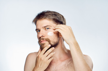 Young guy with a beard on a light background, cosmetic face cream