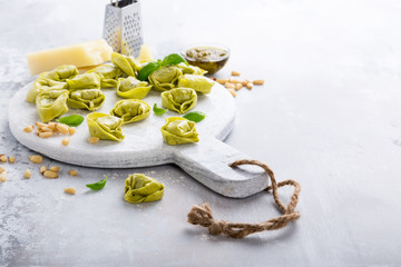 Homemade raw Italian tortelloni and ingredients for green pesto on marble cutting board on light gray background. Healthy food concept. Selective focus. Copy space.
