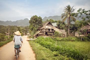 Fotoväggar - Asiatischer Fahrradfahrer in einem Dorf