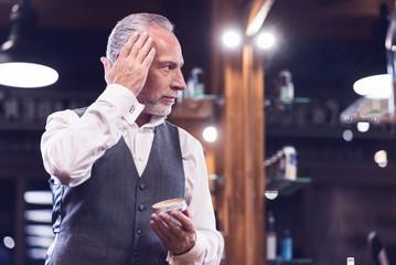 Handsome senior man using hair gel