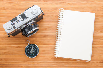 Old camera,compass and notebook on wooden table.