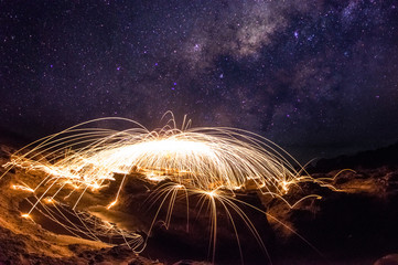 Amazing fireworks, Burning and spinning steel wool on the rock, Showers of hot glowing sparks, Long exposure photo background, Grand canyon of Thailand, The Milky Way galaxy pointing on a bright star.