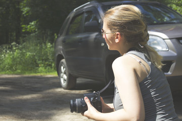 girl near the car taking pictures of nature