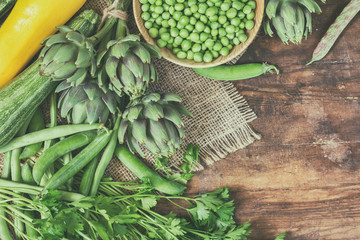 Fresh organic green vegetables wooden floor with copy space. Green and yellow vegetables background. Healthy eating background. Vegetarian food, organic food.