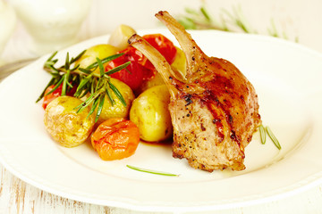 A rack of lamb with potatoes and tomatoes