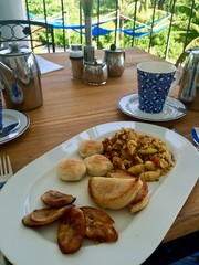 Outside table on the patio with palms: delicious Jamaican breakfast with ackee and saltfish (cod), dumplings, fried banana, plantain, yaam, festival along with fresh hot tea in Port Antonio, Jamaica