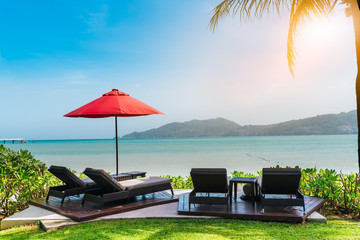 Modern wooden beach chair with red umbrella on tropical beach with blue sky day noon light at Phuket, Thailand.