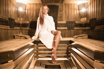 298e033f55 Young woman sitting on wooden bench in sauna