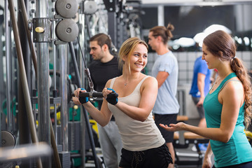 Active young people having weightlifting training