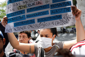 A protester holds a sign in front of the Venezuelan Social Security Institute during a protest due to the shortages of basic medical supplies in Caracas