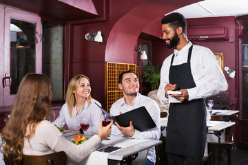 Young cheerful waiter taking care of adults