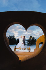 Bride and groom in the heart-shaped frame