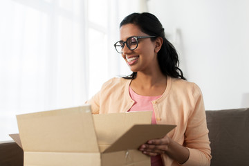 happy young indian woman with parcel box at home