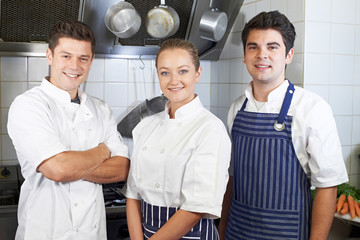 Portrait Of Chef And Staff Standing By Cooker In Kitchen